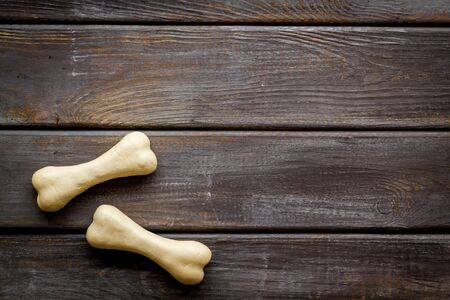 Food and toys for dogs. Chewing bones on dark wooden background top view.