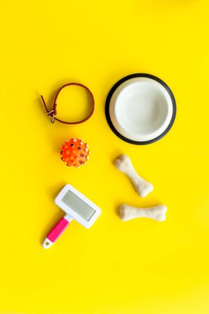 Set of treats and toys for pets with bones, collar and bowl on yellow background top view Фото со стока - 132656606