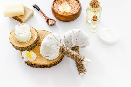 Massage thai herbal balls near spa accessories on white background Stock Photo