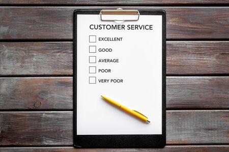 Customer service form on dark wooden background top view.