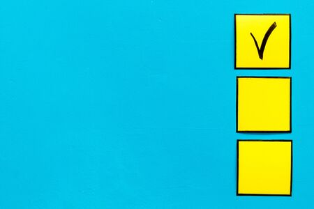 Check mark in yellow check-box on blue background top view.