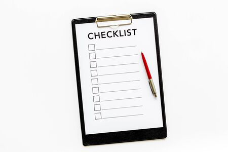 Checklist and pen on white background top view.