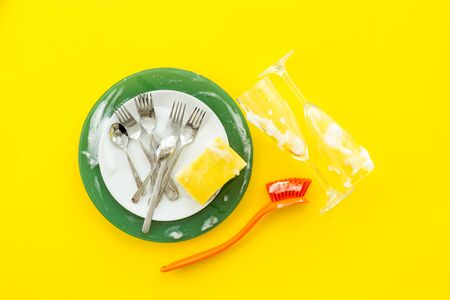 Washing dishes concept. Plates, spoons, forks on yellow background top view. Stock Photo