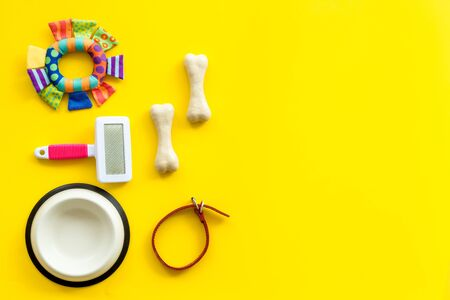 Pet's accessories like bones, collar and bowl on yellow background top view. Фото со стока - 132750103