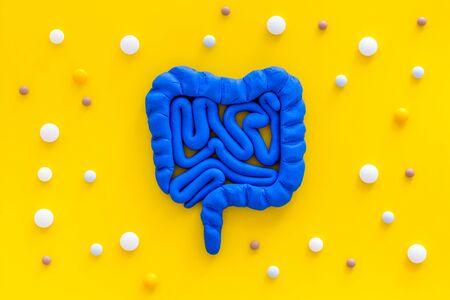 Intestines illness and treatment. Guts near pills on yellow background top view Stockfoto