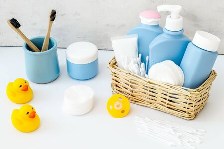 Baby bathroom cosmetics near pacifier and rubber duck on white background