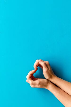 Heart icon. Hands forming a heart on blue background top view copy space