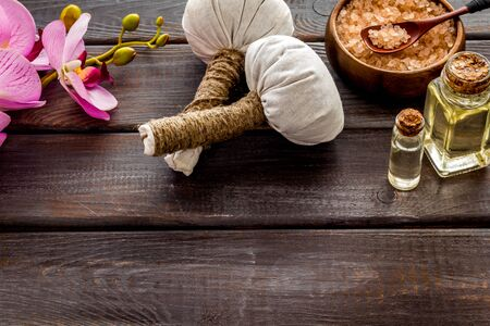 Massage thai herbal balls near spa accessories and orchids on dark wooden background space for text Stock Photo