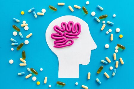 Treat brain diseases. Head with plastiline meanders and pills on blue background top view