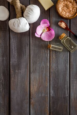 Massage table with thai herbal balls and orchids on dark wooden background top view. Stock Photo