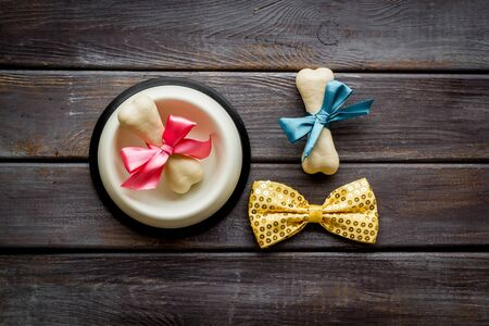 Dogs birthday concept. Chewing bones with bow and bow-tie on dark wooden background top view Фото со стока - 132851239