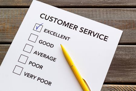 Customer service form close up on dark wooden background top view.