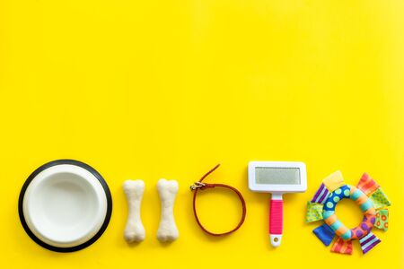 Pets accessories like bones, collar and bowl on yellow background top view flat lay frame copy space Фото со стока - 132808413