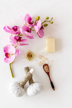 Massage table with thai herbal balls and orchids on white background top view pattern Stock Photo - 132851420