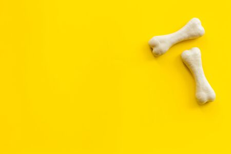 Treats for dogs. Chewing bones on yellow background top view copy space Фото со стока - 132808713