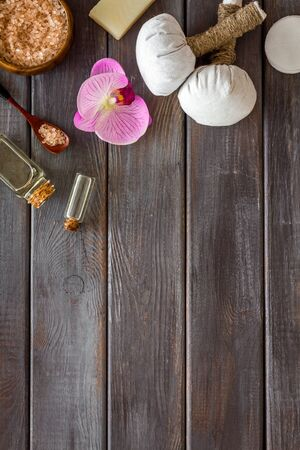 Massage table with thai herbal balls and orchids on dark wooden background top view frame copy space Stock Photo