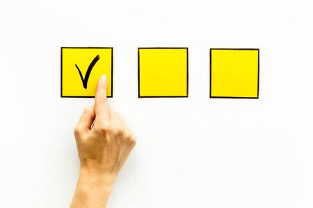 Hand put check mark in yellow check-box on white background top view copy space