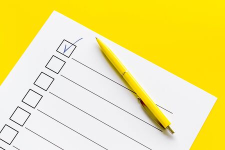 Empty check list ready to fill on yellow background top view