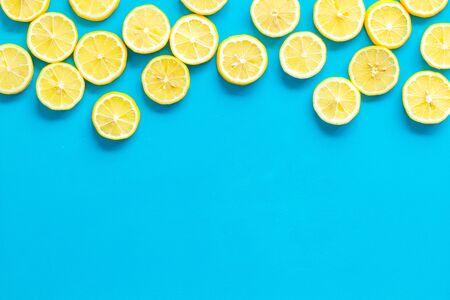 Lemon frame. Sliced citruses on blue background top view copy space