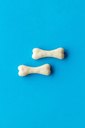 Treats for dogs. Chewing bones on blue background top view space for text Фото со стока