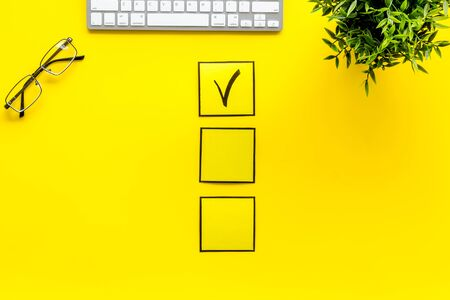 Customer experience concept. Check mark on yellow office desk top view.