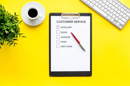 Customer service form on yellow office desk top view copy space