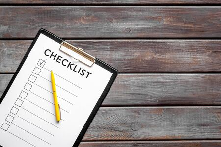 Checklist and pen on dark wooden background top view space for text