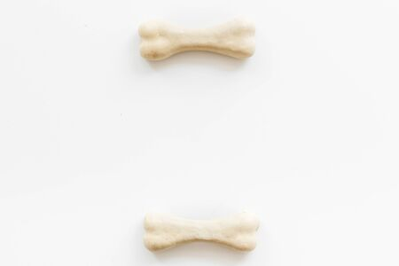 Treats for dogs. Chewing bones on white background top view copy space Фото со стока