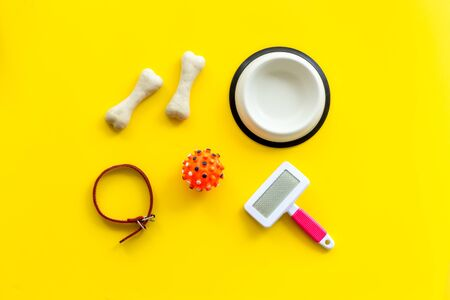 Set of treats and toys for pets with bones, collar and bowl on yellow background top view