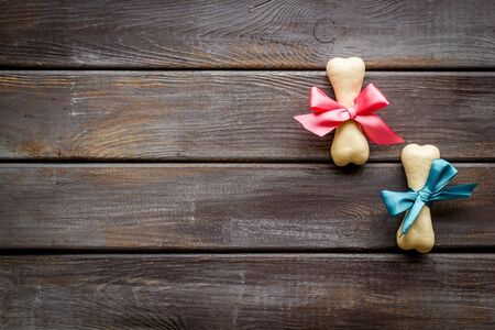 Small present for dogs. Chewing bones with bow on dark wooden background top view space for text