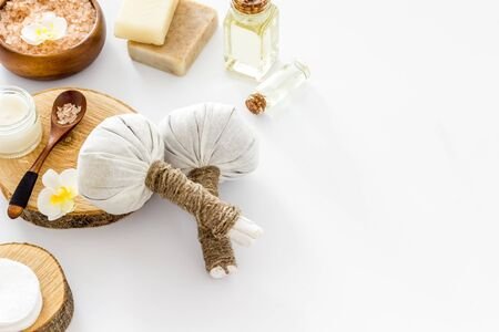 Massage thai herbal balls near spa accessories on white background copy space