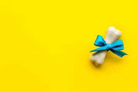 Small present for dogs. Chewing bones with bow on yellow background top view space for text