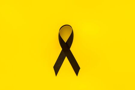 Disease control concept. Black ribbon on yellow background top view space for text Banco de Imagens