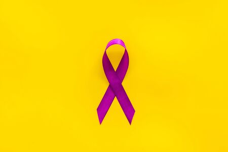 Lavender ribbon is symbol of Alzheimers disease on yellow background top view copy space