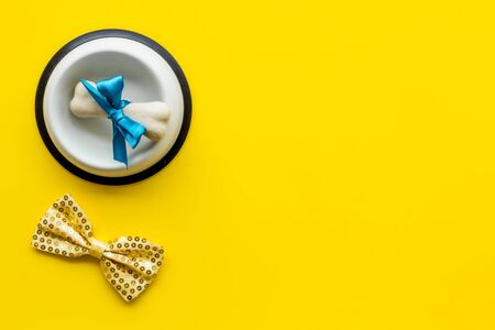 Dog's birthday concept. Chewing bones with bow and bow-tie on yellow background top view. Фото со стока - 133032179