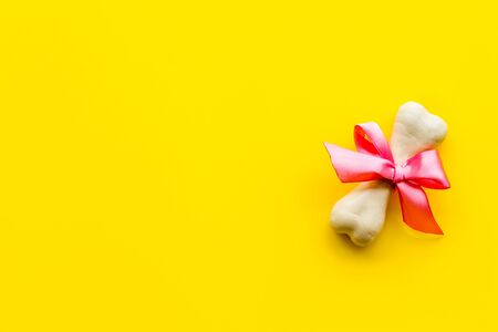 Small present for dogs. Chewing bones with bow on yellow background top view. Фото со стока - 133032008
