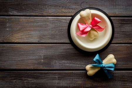 Dogs birthday concept. Chewing bones with bow in bowl on dark wooden background top view space for text
