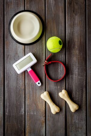 Pets accessories like bones, collar and bowl on dark wooden background top view flat lay Фото со стока - 133225289