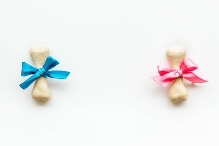 Small present for dogs. Chewing bones with bow on white background top view copy space Фото со стока