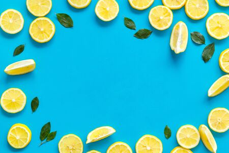 Lemon frame. Sliced citruses and leaves on blue background top view copy space