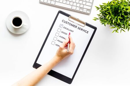 Service quality assessment. Hand fill customer service form on white office desk top view
