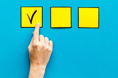 Hand put check mark in yellow check-box on blue background top view.