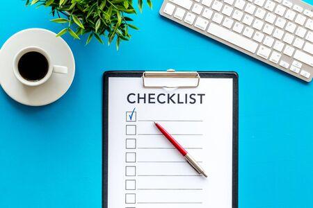 Lista di controllo e penna sulla vista superiore del fondo blu dell'ufficio