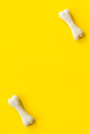 Treats for dogs. Chewing bones on yellow background top view. Фото со стока
