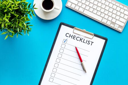 Checklist and pen on blue office background top view. Stock Photo