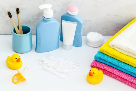 Cute bathroom cosmetics set with yellow rubber duck on white background. Banco de Imagens