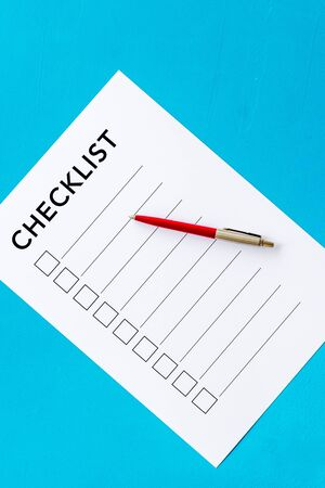 Checklist and pen on blue background top view.