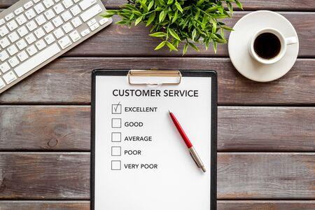 Customer service form on dark wooden office desk top view.
