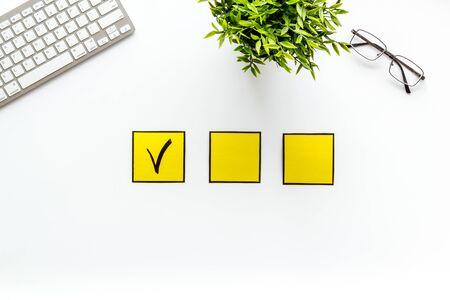 Customer experience concept. Check mark on white office desk top view. Reklamní fotografie