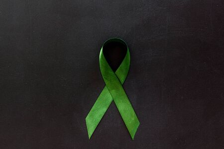 Green ribbon as symbol of disease control on white background top view copy space